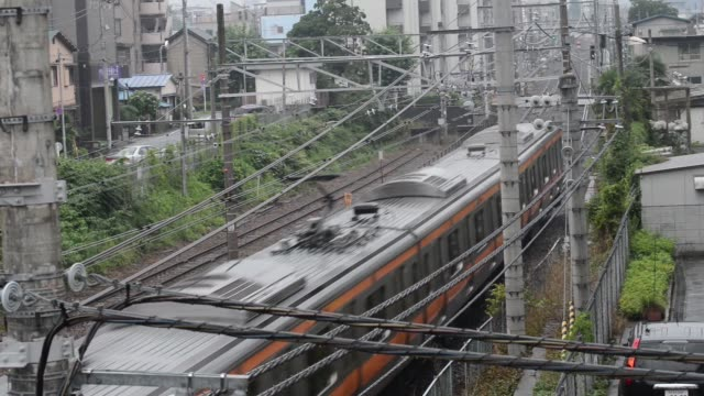 wide shot, a train passes along electric cables suspended above railroad of jr line in tokyo, wide shot, a train arrives a platform at jr hachioji... - ナイトイン点の映像素材/bロール