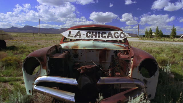 vidéos et rushes de wide shot abandoned car with sign on windshield pointing directions to los angeles and chicago / holbrook, arizona - route 66