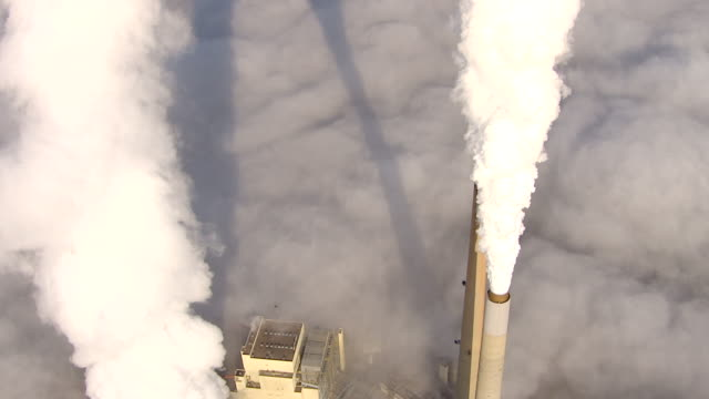 wide shot aerial , a coal power plant spews steam into the sky. / west virginia - coal fired power station stock videos and b-roll footage