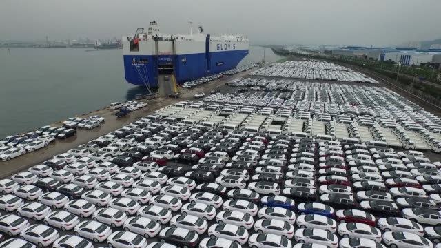wide shot, aerial, birds eye view, rising over hyundai motor co vehicles bound for export waiting to board a hyundai glovis co roll-on/roll-off cargo... - automobilindustrie stock-videos und b-roll-filmmaterial