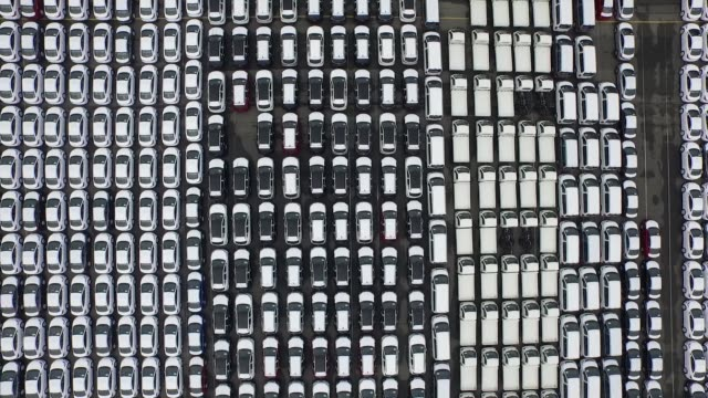 wide shot, aerial, birds eye view, static to sideways left flying over hyundai motor co vehicles bound for export waiting to board a hyundai glovis... - automobilindustrie stock-videos und b-roll-filmmaterial