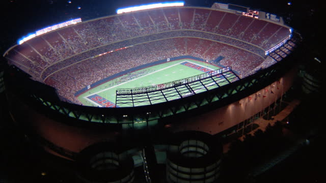 1986 wide shot aerial circling giants stadium at night with game in progress / east rutherford, new jersey - stadio video stock e b–roll