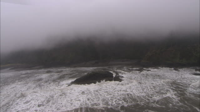vidéos et rushes de wide shot aerial - fog shrouds a rugged ocean coastal area - overcast