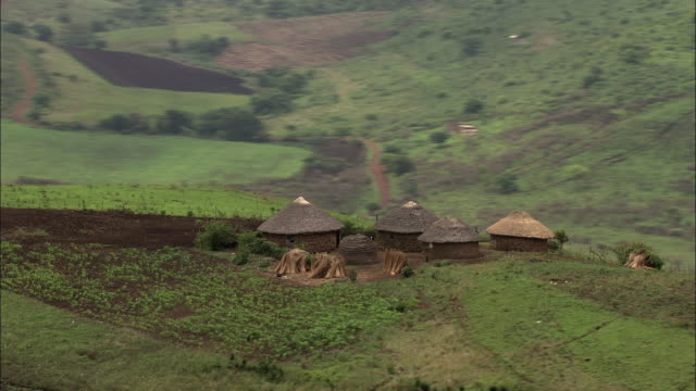 wide shot aerial pan-left push-out tracking-right - lush, rolling hills and  farmland surround village huts in south africa. / south africa - indigenous culture stock videos & royalty-free footage