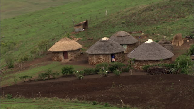 wide shot aerial pan-left tracking-right - farmland surrounds village huts in south africa. / south africa - strohdach stock-videos und b-roll-filmmaterial