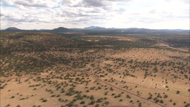wide shot aerial push-in - a deserted arizona road crosses the desert toward distant mountains. / arizona, usa - shrubland stock videos & royalty-free footage