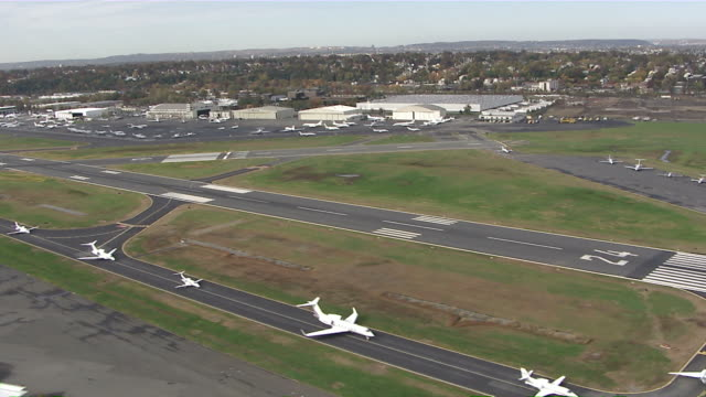 wide shot  aerial push-in - airplanes line up on an airport runway. /  usa - アスファルト点の映像素材/bロール