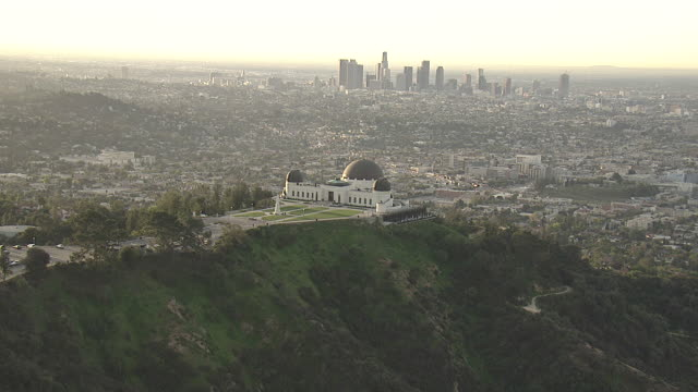 wide shot aerial push-in - downtown los angeles skyscrapers tower beyond the griffith observatory. / los angeles, california, usa - urban sprawl stock videos & royalty-free footage