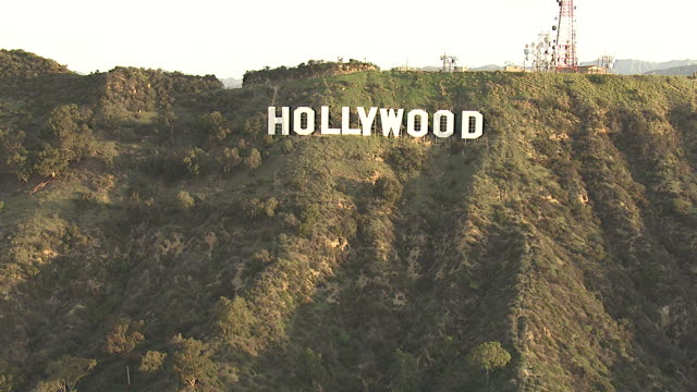 Wide Shot aerial push-in - The famous Hollywood sign towers on the Hollywood Hills. / Los Angeles, California, USA