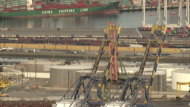 Wide Shot aerial push-out - Cranes rise over a container ship at the Long Beach port. / Los Angeles, California, USA
