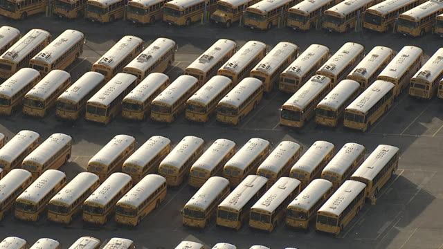 stockvideo's en b-roll-footage met wide shot aerial push-out - rows of school buses line a parking lot. / los angeles, california, usa - blijf staan