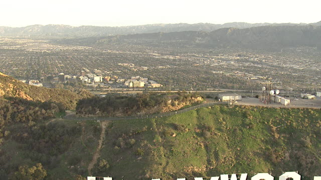 Wide Shot aerial push-out - The Hollywood Hills of Los Angeles feature the famous Hollywood sign. / Los Angeles, California, USA