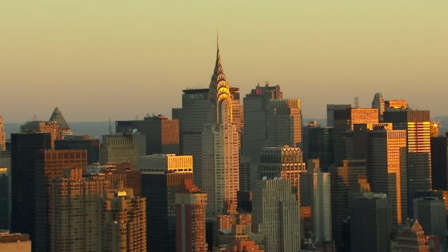 wide shot  aerial push-out tracking-right - the chrysler building towers amid other skyscrapers in manhattan. /  new york city - chrysler building stock videos & royalty-free footage