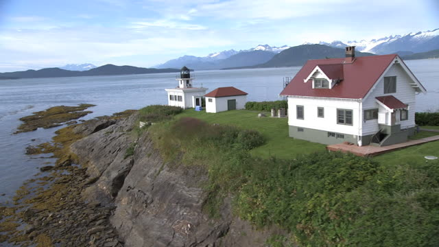 """Wide Shot aerial push-out-A green lawn surrounds a small white house and lighthouse on the Alaskan coast. / Alaska, USA"""