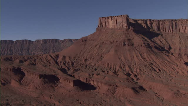 Wide Shot aerial - Steep cliffs rise above a desert / Grand Canyon, USA