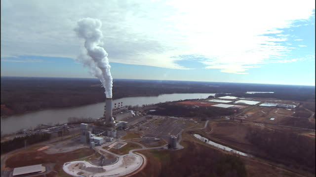 Wide Shot aerial tracking,left , A tall smokestack spews steam into the air. / Charlotte, North Carolina, USA