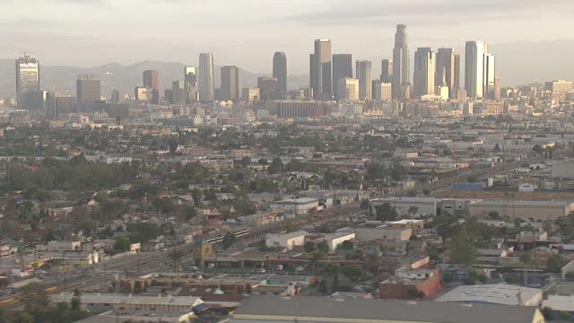 vídeos de stock e filmes b-roll de wide shot aerial tracking-left - the los angeles skyline towers beyond a suburb. / los angeles, california, usa - expansão urbana