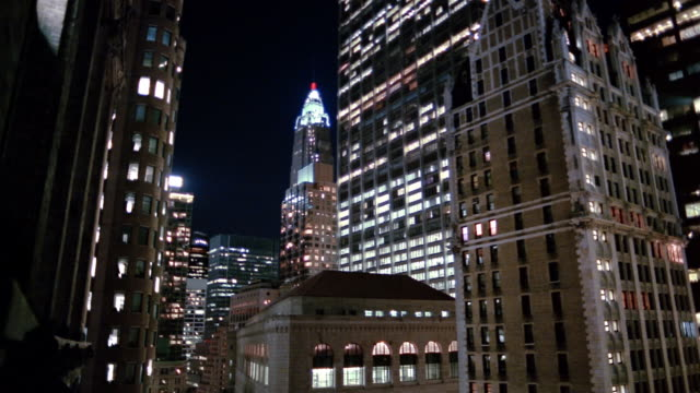 Wide shot AIG Building, Chase Manhattan Bank Tower, Federal Reserve Bank and Liberty Tower at night / NYC