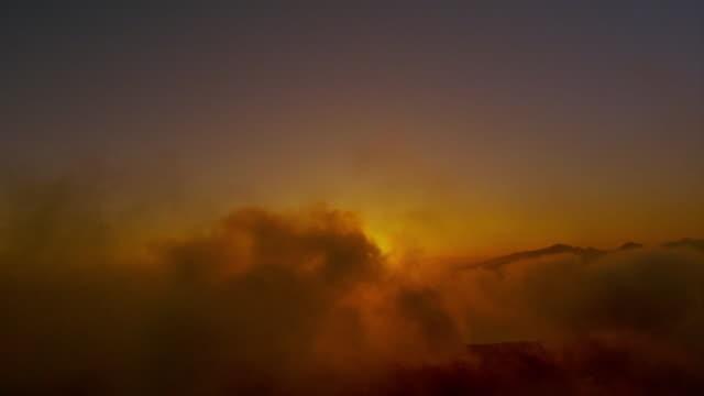 aerial wide shot aircraft point of view through orange clouds toward sunrise over ocean + coastline / hawaii - romantische stimmung stock-videos und b-roll-filmmaterial