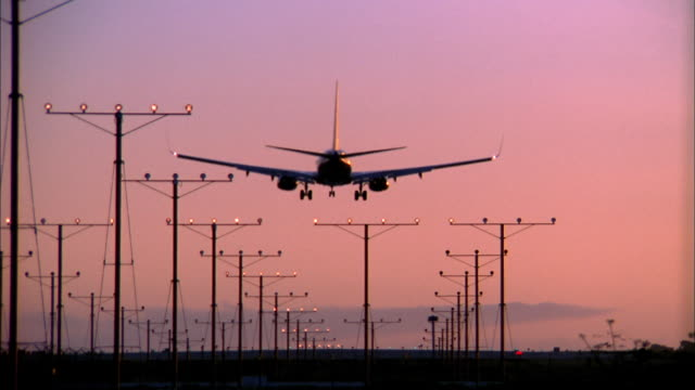 Wide shot airplane landing at sunset w/light towers on runway / low angleX