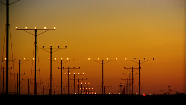 vídeos de stock e filmes b-roll de wide shot airplane landing at sunset w/light towers on runway / low anglex - aeroporto internacional de los angeles