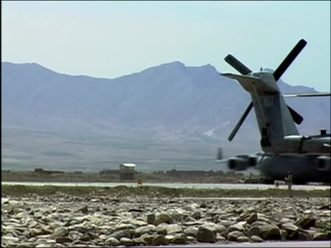 Wide shot airplane on runway passing by tail of parked plane at Bagram Air Base / Bagram Afghanistan / AUDIO