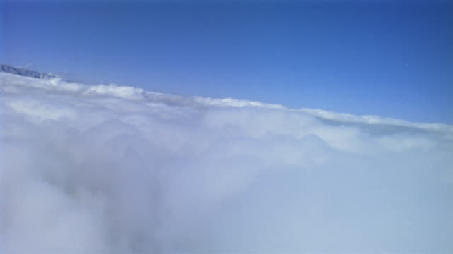 vídeos de stock e filmes b-roll de wide shot airplane point of view flying through fluffy white clouds - vista inclinada