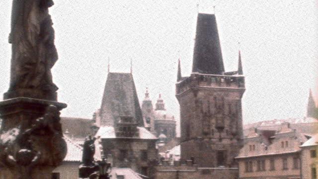 OVEREXPOSED wide shot PAN along rooftops + bridge towers of Charles Bridge / Prague, Czech Republic