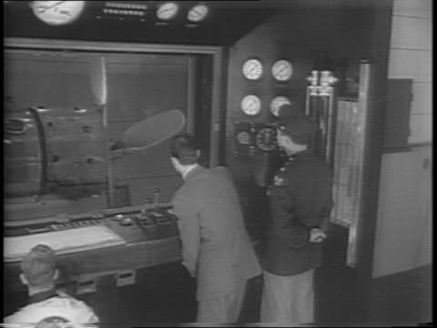 wide shot and pan of the control room with people in room peering out of glass window next to control room with propeller spinning / medium shots of... - porous stock videos & royalty-free footage