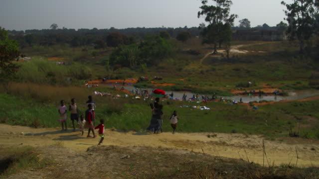 stockvideo's en b-roll-footage met wide shot, angolan family walks down path - wasmand