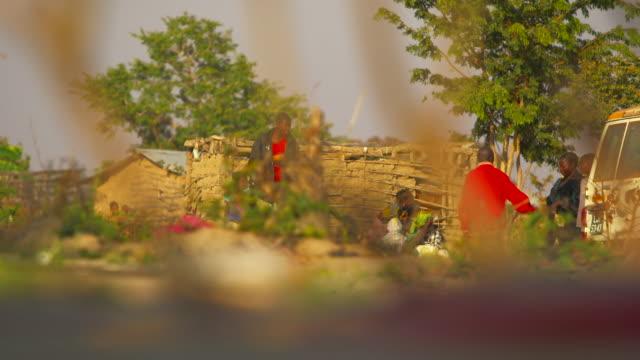 wide shot angolan villagers to close up of metal detector - säkerhetsskanner bildbanksvideor och videomaterial från bakom kulisserna