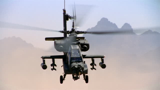 wide shot apache helicopter flying toward cam in cloud of dust / flying over cam / california - アパッチヘリコプター点の映像素材/bロール