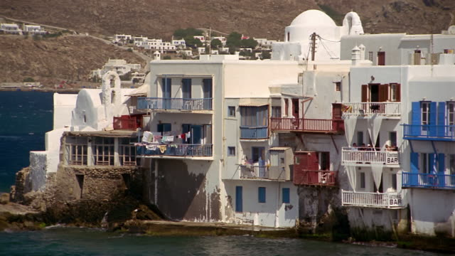 Wide shot apartment building on the water in the town of Little Venice / Mykonos, Greece