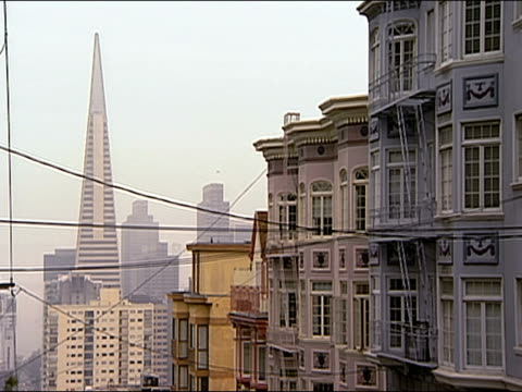 vidéos et rushes de wide shot apartment buildings and transamerica pyramid in the distance / san francisco, california - transamerica pyramid san francisco