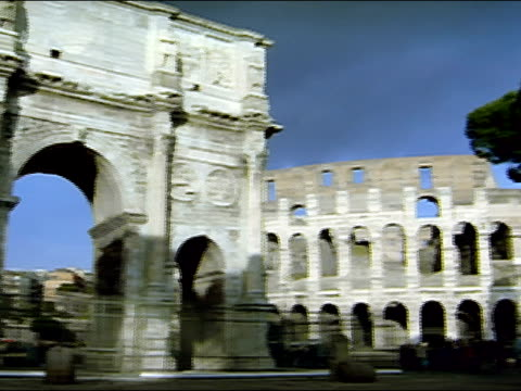 wide shot arch of constantine / pan to view of exterior coliseum / rome, italy - arch of constantine stock videos and b-roll footage