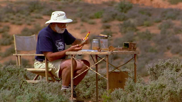 Wide shot archeologist working with bone at folding table in desert