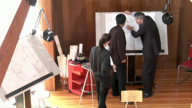 wide shot architects looking at blueprint - 製図板点の映像素材/bロール