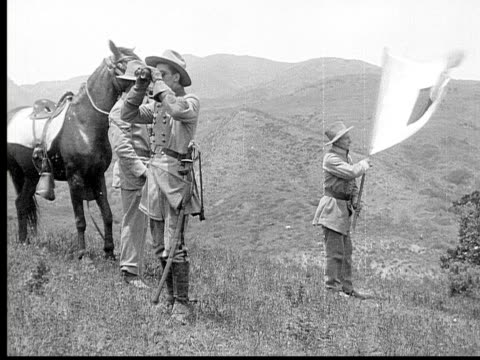 1913 reenactment b/w wide shot army officer looking through binoculars on battlefield and signaling to soldier to wave flag while another officer rides toward them on horseback / usa  - 1913 stock videos & royalty-free footage