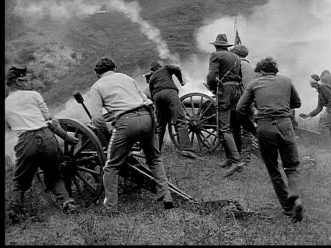 1913 reenactment b/w wide shot army officer looking through binoculars while soldiers load and fire cannons on battlefield during civil war battle reenactment / usa  - 1913 stock videos & royalty-free footage