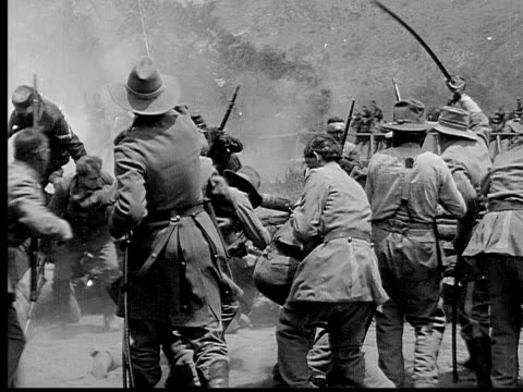 1913 REENACTMENT B/W Wide shot Army officers and soldiers fighting with swords and rifles during Civil War battle reenactment / USA