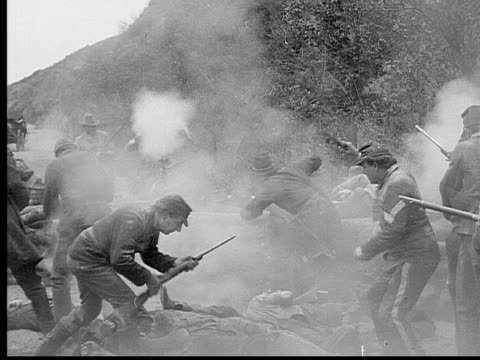 1913 REENACTMENT B/W Wide shot Army officers and soldiers shooting at each other with rifles and pistols during Civil War battle reenactment / USA