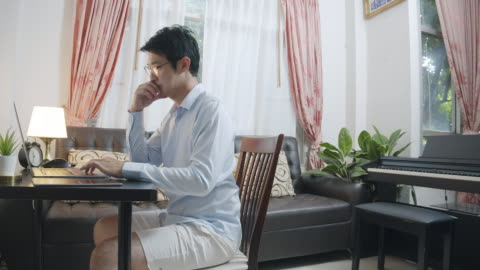 wide shot asian man wearing blue shirt on top and shot sport pant on bottom while video conference with his business partnership on laptop computer. talking with friend via online meeting or video call technology. working from home. - trousers stock videos & royalty-free footage