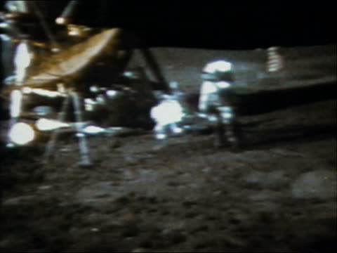 1971 wide shot astronaut Alan Shepard swinging a soil sampler like a golf club on the surface of the moon