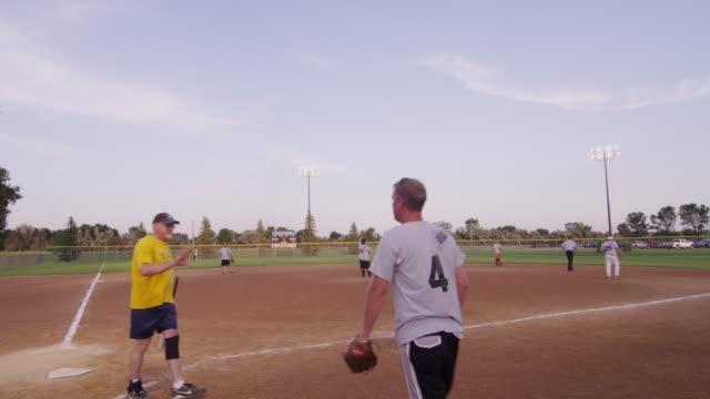 vídeos y material grabado en eventos de stock de wide shot at a men's league softball game, pitch is made, hit to center field. - sófbol