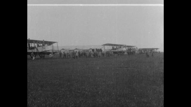 Wide shot at a Trentino airfield with line of biplanes and ground crew near them / close shot of a pilot in his plane with propeller moving and an...