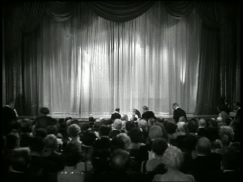 1934 b/w wide shot audience in theatre applauds as curtain opens / men in tuxedos start tap dancing on stage - 演劇点の映像素材/bロール