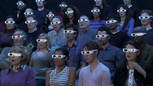 vídeos de stock, filmes e b-roll de wide shot audience wearing 3-d glasses reacting to movie out of frame with shock and pleasure - óculos de terceira dimensão