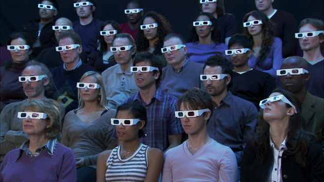 wide shot audience wearing 3-d glasses reacting to movie out of frame with shock and pleasure - film industry stock videos & royalty-free footage