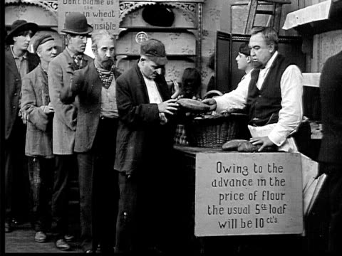 stockvideo's en b-roll-footage met 1909 b/w wide shot baker giving free bread to line of hungry men/ baker running out bread and turning customers away  - 1900 1909