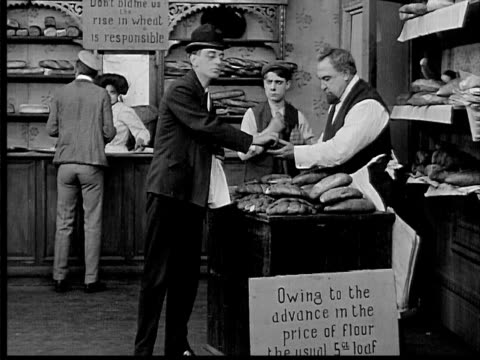 1909 b/w wide shot baker selling bread with signs explaining higher prices - 1900 1909 stock-videos und b-roll-filmmaterial